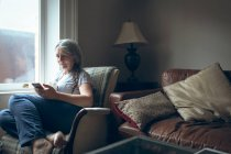Senior woman using mobile phone in living room at home — Stock Photo