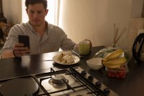 Disabled man using mobile phone on dining table at home — Stock Photo