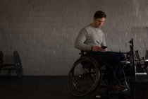 Young disabled man using mobile phone in workshop — Stock Photo