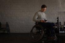 Jeune homme handicapé utilisant un téléphone portable en atelier — Photo de stock