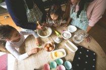 Familie bereitet Frühstück am Esstisch zu Hause — Stockfoto