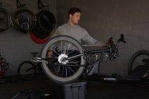 Jeune handicapé homme en fauteuil roulant à l'atelier de réparation — Photo de stock