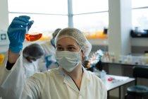 Cientista feminina atenta experimentando em laboratório — Fotografia de Stock