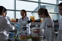 Team of scientists experimenting together in laboratory — Stock Photo