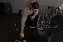 Giovani disabili uomo in sedia a rotelle a officina di riparazione — Foto stock