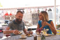 Happy couple having breakfast in outdoor cafe — Stock Photo