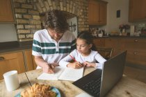 Father helping her daughter in studies at home — Stock Photo