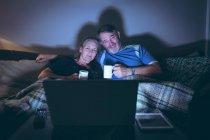 Feliz pareja de ancianos viendo el ordenador portátil mientras toma café en casa - foto de stock