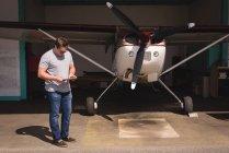 Mann mit digital-Tablette am Hangar an einem sonnigen Tag — Stockfoto