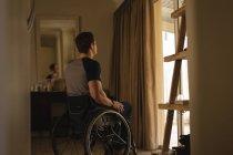 Homme handicapé réfléchi en fauteuil roulant à la maison — Photo de stock