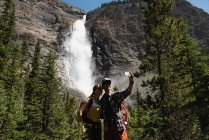 Couple taking selfie with mobile phone near waterfall — Stock Photo