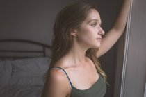 Réfléchie femme regardant par la fenêtre à la maison — Photo de stock