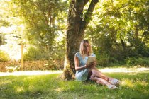 Jeune femme à l'aide de la tablette numérique dans le parc — Photo de stock