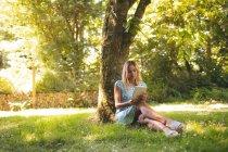 Junge Frau nutzt digitales Tablet im Park — Stockfoto