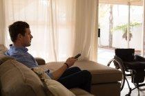 Homme handicapé changer de canal dans le salon à la maison — Photo de stock