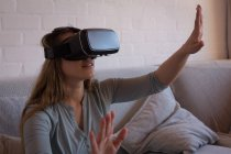 Woman using virtual reality headset on sofa at home — Stock Photo