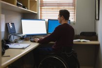 Disabled man working on computer at home — Stock Photo