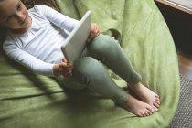 Накладні дівчина, використовуючи цифровий планшетний у вітальні на дому — стокове фото