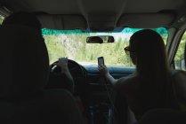 Vue arrière du couple voyageant en voiture — Photo de stock