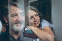 Thoughtful senior couple looking through window at home — Stock Photo