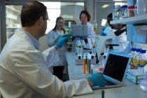 Cientista masculina usando laptop, mantendo o tubo de ensaio em laboratório — Fotografia de Stock