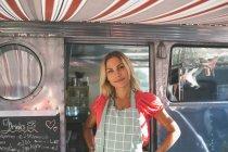 Beautiful female waitress standing in food truck — Stock Photo