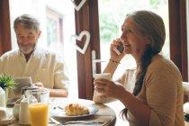 Ältere Frau am Handy beim Kaffeetrinken zu Hause — Stockfoto