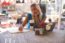 Attentive woman writing on a book in outdoor cafe — Stock Photo