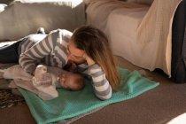 Мать кормит молочной бутылкой на полу дома — стоковое фото