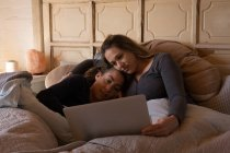 Coppia lesbica utilizzando il computer portatile sul letto a casa — Foto stock