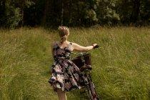Vista trasera de la mujer caminando con bicicleta en el campo - foto de stock