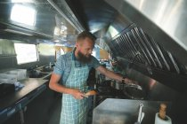 Handsome waiter preparing food in food truck — Stock Photo