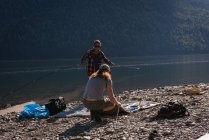 Couple setting up tent near riverside — Stock Photo