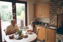 Casal sênior tomando café na cozinha em casa — Fotografia de Stock