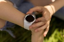 Close-up of woman using smartwatch in the field — Stock Photo