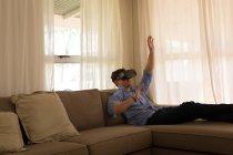 Человек, использующий гарнитуру виртуальной реальности в гостиной дома — стоковое фото