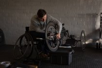 Young disabled man repairing wheelchair at workshop — Stock Photo
