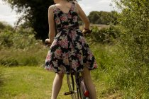 Mid section of woman riding bicycle in the field — Stock Photo