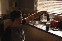 Инвалид готовит кофе на кухне дома — стоковое фото
