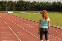 Rear view of female athlete standing on sports track — Stock Photo