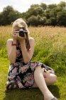Женщина щелкает фото с цифровой камерой в поле — стоковое фото