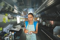 Woman waitress writing orders on notepad in food truck — Stock Photo