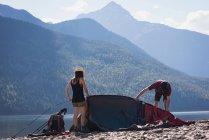 Paar, die Vorbereitung für das Einrichten von einem Zelt an einem sonnigen Tag machen — Stockfoto