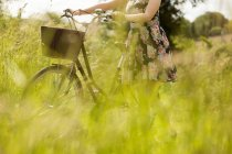 Mid section of woman walking with bicycle in the field — Stock Photo