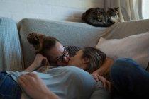 Лесбиянки целуются дома на диване — стоковое фото