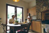 Pareja mayor interactuando entre sí mientras desayunan en casa - foto de stock
