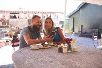 Couple romantique prenant selfie sur téléphone portable dans un café extérieur — Photo de stock