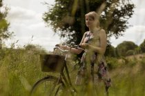 Woman walking with bicycle in the field at countryside — Stock Photo