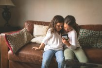 Девушки, использующие мобильный телефон на диване дома — стоковое фото