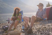 Couple camping near riverside in mountains — Stock Photo